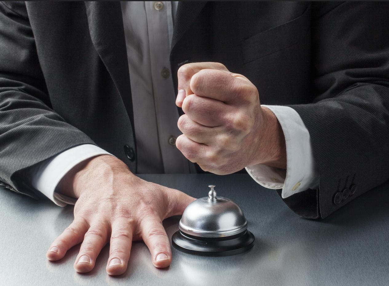 Niezadowolony gość uderza w dzwonek na biurku recepcjonisty